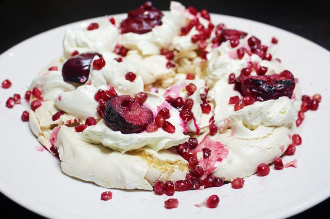 meringue wreath with mulled plums and pomegranates